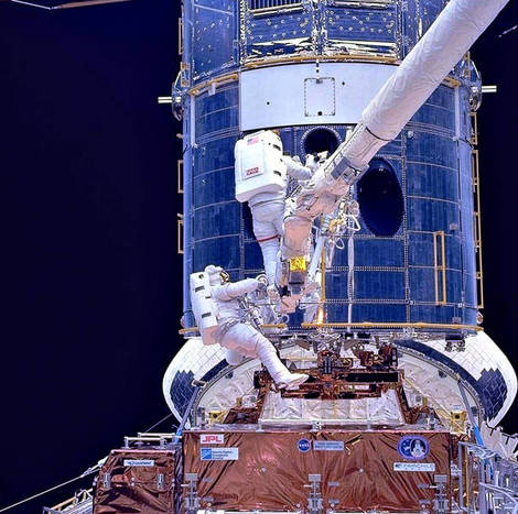 astronauts work on the hubble telescope.