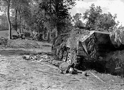 An armored SdKfz 251 half-track of the 2.SS-Panzer division (Das Reich) and the corpse of a German soldier near Mortain 1944.