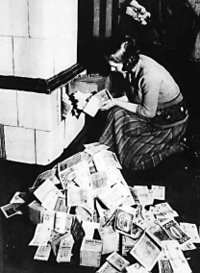 Inflation 1923-24: a woman feeds her tiled stove with money