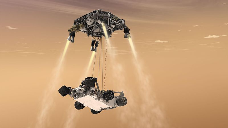 Artist's concept of the Curiosity rover, as it is being lowered by the sky crane from the rocket-powered descent stage.