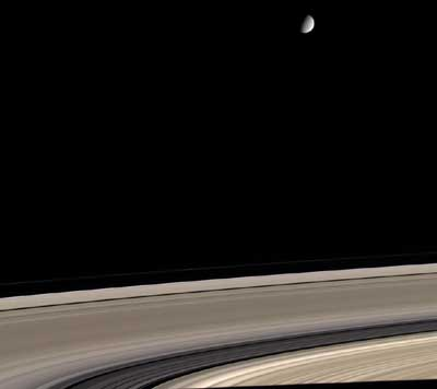 Saturn's icy Moon Enceladus above the planet's sweeping rings.